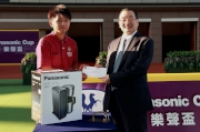 Mr Terrence Chan, Vice Chairman of Shun Hing Group, presents a prize of HK$1,500 and a Panasonic coffee maker to the Stables Assistant responsible for Rewarding Hero, the best turned out horse in the Panasonic Cup.