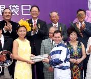依照莎莎婦女銀袋賽的傳統,得勝馬匹「包裝鬥士」的騎師杜滿萊於賽後在頒獎儀式上致送名貴手袋予頒獎嘉賓梁偉妍小姐。