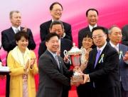 澳門賽馬會執行董事兼行政總裁李柱坤先生(右)頒發澳港盃獎盃予頭馬「夢仙」的練馬師葉楚航。