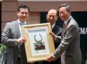 馬主林培雄 (中) 及林顯裕 (左) 致送「雄心威龍」的馬蹄鐵予香港賽馬會主席葉錫安博士 (右)。