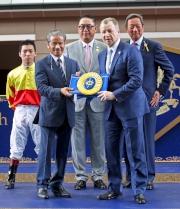香港賽馬會行政總裁應家柏致送紀念綵帶予練馬師告東尼。