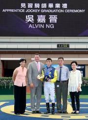 吳嘉晉及其家人與香港賽馬會賽馬事務執行總監利達賢(左二)、及賽馬培訓發展委員會經理暨見習騎師學校校長陳念慈(左一)於畢業禮上合照。