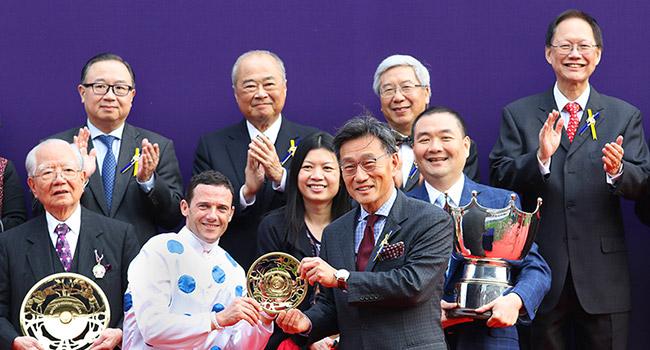 馬會董事鄭維志博士於頒獎禮上,頒發女皇銀禧紀念盃鍍金碟予「詠彩繽紛」的騎師柏寶。