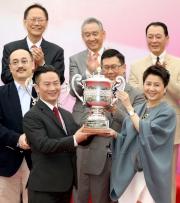澳門賽馬會副主席兼執行董事梁安琪女士(右)將澳港盃冠軍獎盃頒予頭馬「好有運」的練馬師王君適。
