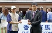 體育專員楊德強先生 (右) 頒發最佳外觀馬匹獎予馬匹「無敵飛龍」的馬房助理 (左)。