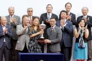 在渣打冠軍暨遮打盃頒獎禮上,馬會董事利子厚(右)頒發冠軍獎盃予頭馬「將男」的馬主代表。