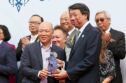 渣打銀行(香港)有限公司大中華及北亞地區行政總裁洪丕正(右),在頒獎禮上頒發紀念品予「將男」的馬主代表。