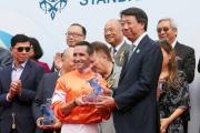 渣打銀行(香港)有限公司大中華及北亞地區行政總裁洪丕正(右)頒發紀念品予「將男」的騎師郭能。