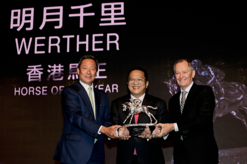 """Werther is crowned Horse of the Year. Dr Simon S O Ip, Chairman of The Hong Kong Jockey Club, presents the trophy to Mr Johnson Chen, owner of Werther. Werther is also winner of """"Champion Middle-Distance Horse"""" and voted """"Most Popular Horse of the Year""""."""