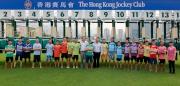馬會賽事規管及發展執行總監夏定安(左十)、賽馬業務及營運執行總監祁立賢(左十二)及今屆騎師競跑大賽的參賽者在比賽前合照。