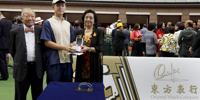 Chairman of the Oriental Watch Holdings Limited Dr Yeung Ming Biu, accompanied by his wife, presents a prize of HK$2,000 and a delicate watch to the Stables representative responsible for Joyful Trinity (middle), the best turned out horse in the Oriental Watch 55th Anniversary Sha Tin Trophy.
