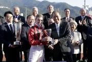 其士國際集團有限公司副董事總經理譚國榮頒發獎盃予「勢必跑」的騎師祈普敦。