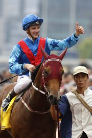 Sam Clipperton salutes after winning the Hong Kong Macau Trophy on the John Moore-trained Invincible Dragon.