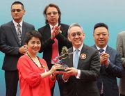 澳門賽馬會副主席兼執行董事梁安琪女士(左)在澳港盃頒獎禮上,致送紀念品予香港賽馬會副主席周永健先生。