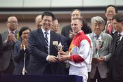 Zac Purton is presented with his trophy for winning the Class 3 18 Districts Cup Handicap (1200m) by Law King-Shing, the Duty Chairman of 18 District Councils and Chairman of Kwai Tsing District Council. It was also the rider��s 700th win in Hong Kong.