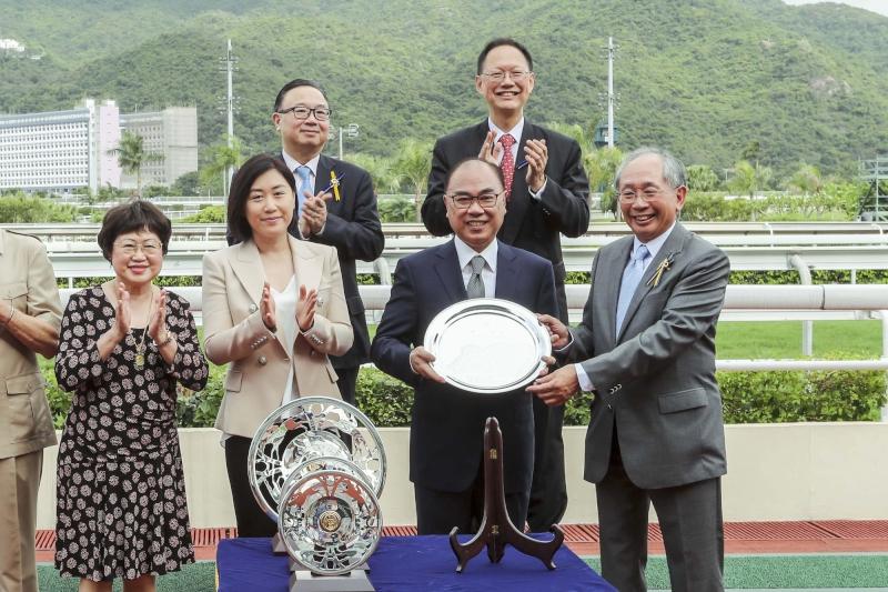 馬會董事郭志桁先生於頒獎禮上將獅子山錦標的獎盃及冠軍銀碟頒予「喜旺寶 」的馬主羅建生、練馬師約翰摩亞及騎師祈普敦 。