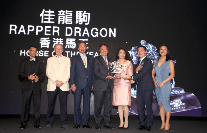 Rapper Dragon is crowned Horse of the Year. Dr. Simon Ip, Chairman of HKJC, presents the trophy to owner Mr. Albert Hung Chao Hong, accompanied by trainer John Moore, jockey Joao Moreira and Mr. Hung's family.