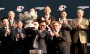 香港賽馬會主席施文信(右)頒發浪琴表香港一哩錦標獎盃予「精彩日子」馬主百家樂團體的代表。