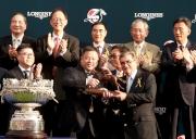 香港賽馬會主席施文信(右)頒發騎師駿馬銅像予「精彩日子」馬主百家樂團體的代表 。