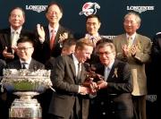 香港賽馬會主席施文信(右)頒發騎師駿馬銅像予「精彩日子」的練馬師蔡約翰。